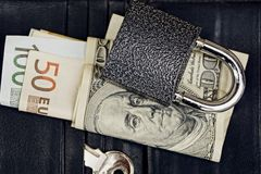 Lock with key and currency on purse. Money on a black leather wallet with a lock and a key Stock Images