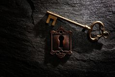 Lock and key. Vintage lock with gold key on dark textured background Royalty Free Stock Photo