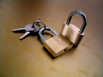 Lock and Keys. Two padlocks and a set of keys on a gold background royalty free stock image