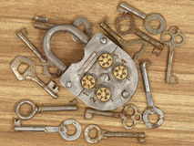 Lock and keys. Old metal lock and keys on a wooden table background royalty free stock photography