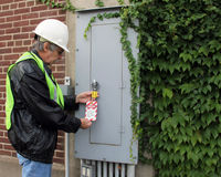Lock out safety tag. Electrician places a safety lock out tag on a breaker panel Royalty Free Stock Images
