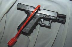 Lock securing gun. Large lock securely fastening gun or pistol to smooth surface royalty free stock images