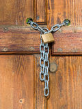 Lock  and shiny chain closing a wooden garden gate Stock Photography