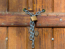 Lock  and shiny chain closing a wooden gate Royalty Free Stock Photo