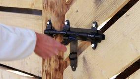 Lock shutter in the wooden door. The man closes the shutter black lock on a wooden door stock video