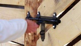 Lock shutter in the wooden door. The man opens the shutter black lock on a wooden door stock video footage