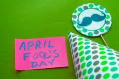 Lock topper med mustaschen, bokstäver för dag för ` s för April dumbom på grön bakgrund Royaltyfri Fotografi