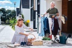 Lockande blondin-haired kvinna som bär den gjorde randig klänningen som ser skor på gårdförsäljningen arkivfoton