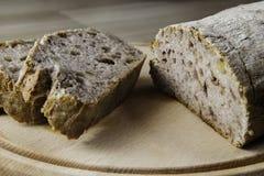Lockande bröd och brödskivor på den wood skärbrädan Arkivfoton
