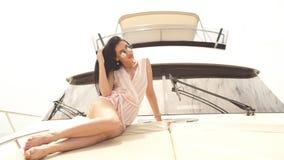 Lockande kvinna som garvar på yachten och att tycka om solljus som poserar på däck av det moderna fartyget arkivfilmer