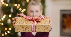Young Woman Showing Her Christmas Gift At Home