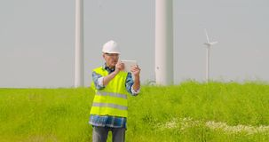 Male engineer video conferencing against windmills. Lockdown shot of confident mature male engineer video conferencing and pointing at windmills while standing stock video footage
