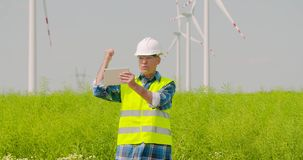 Male engineer video conferencing against windmills. Lockdown shot of confident mature male engineer video conferencing and pointing at windmills while standing stock footage