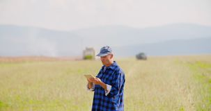 Modern farming agriculture. Lockdown shot of mature farmer using digital tablet while looking at tractor on field
