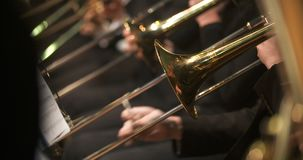 Musician playing trumpet during concert. Lockdown shot of musician playing trumpet, French horn. Male is using brass instrument during a concert. He is wearing stock video footage