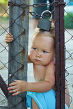 Locked baby trying to escape through wire fencing. Locked baby boy trying to escape through wire fencing with padlock. outdoors Royalty Free Stock Images