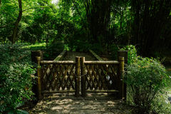 Locked bamboo-made door at head of stone bridge in woods of sunn royalty free stock photography