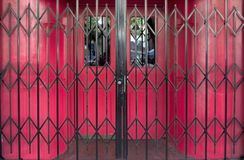 Locked Bar Gates. Security gates block the red doors of a closed bar royalty free stock photography