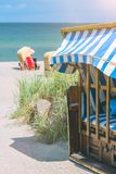 Locked blue colored roofed chairs on sandy beach in Travemunde, Germany.  royalty free stock photos