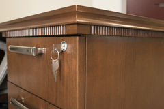 Locked desk drawer. Close-up of desk drawer with key inserted Royalty Free Stock Photography