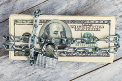 Locked dollars on wooden background. Stock Photography