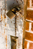 Locked Door. Shallow depth of focus view of a padlock on an old paint chipped door Stock Photography