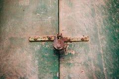 Locked door. Closed old rusty padlock on a distressed wooden door Royalty Free Stock Photo