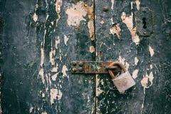 Locked door. Closed old rusty padlock on a distressed wooden door Stock Photo