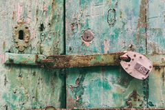 Locked door. Closed old rusty padlock on a distressed wooden door Royalty Free Stock Images