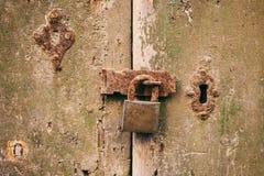 Locked door. Closed old rusty padlock on a distressed wooden door Royalty Free Stock Image