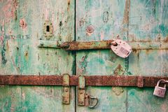 Locked door. Closed old rusty padlocks on a distressed wooden door. Closeup view Stock Photo