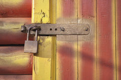 Locked door fragment. Striped wooden door fragment with metallic lock Stock Photography
