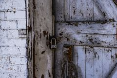 Locked door of a wood shed with peeling white paint royalty free stock photos