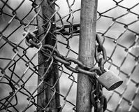Locked Fence B&W. A padlocked chain link fence in black and white Stock Photo