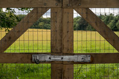 Locked fence by field Stock Photo