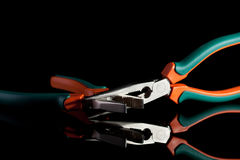 Locked flat nose and needle nose pliers. On black background Royalty Free Stock Photography
