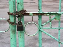 Locked gate. Green gate, chain and padlock Royalty Free Stock Photos