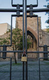 A locked gate, with a church in the background Stock Photos