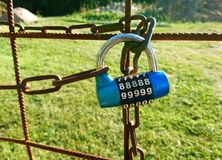 Locked gate. Closeup of a locked gate to a garden with a code lock and chain Royalty Free Stock Images