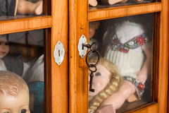 Locked glass cabinet with antique dolls. Stock Photo Stock Photography