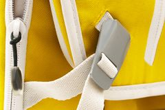 Locked gray metal buckle on white strap. On yellow sports backpack royalty free stock images