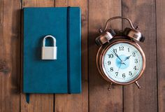 Locked and key on Blue notebook on wooden background stock photography