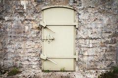 Locked massive metal door in old wall Stock Image