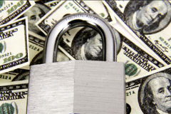 Locked Money. Padlock closed on top of a stack of one hundred dollar bills Royalty Free Stock Image
