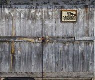 Locked old wooden door with sign. Exterior old door locked with no parking sign royalty free stock images