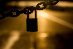Locked Out. Silhouette of chain link and lock at sunset Stock Photos