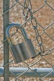 Locked Out. Silver lock and chain hanging on a fence Stock Images