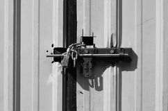 Locked padlock and chained on galvanize metal sheet door, black Stock Photography