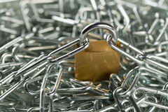 Locked padlock with chains on huge chain heap Royalty Free Stock Photo