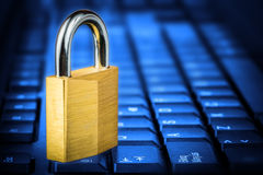 Locked padlock om a glowing blue computer keyboard Stock Photos